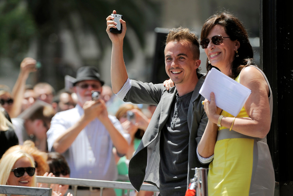 ". Frankie Muniz, left, and Jane Kaczmarek, cast members in the television series ""Malcolm in the Middle,\"" wave to the crowd during a ceremony to award fellow cast member Bryan Cranston a star on the Hollywood Walk of Fame on Tuesday, July 16, 2013 in Los Angeles. (Photo by Chris Pizzello/Invision/AP)"