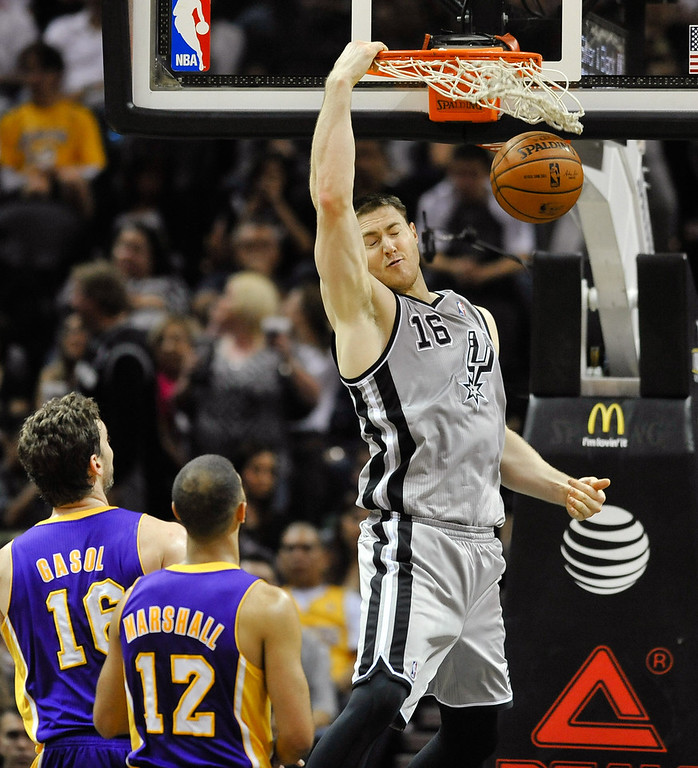 . San Antonio Spurs center Aron Baynes dunks in front of Los Angeles Lakers\' Pau Gasol and Kendall Marshall in the first half of an NBA basketball game Friday, March 14, 2014 in San Antonio. The Spurs won 119-85. (AP Photo/Bahram Mark Sobhani)