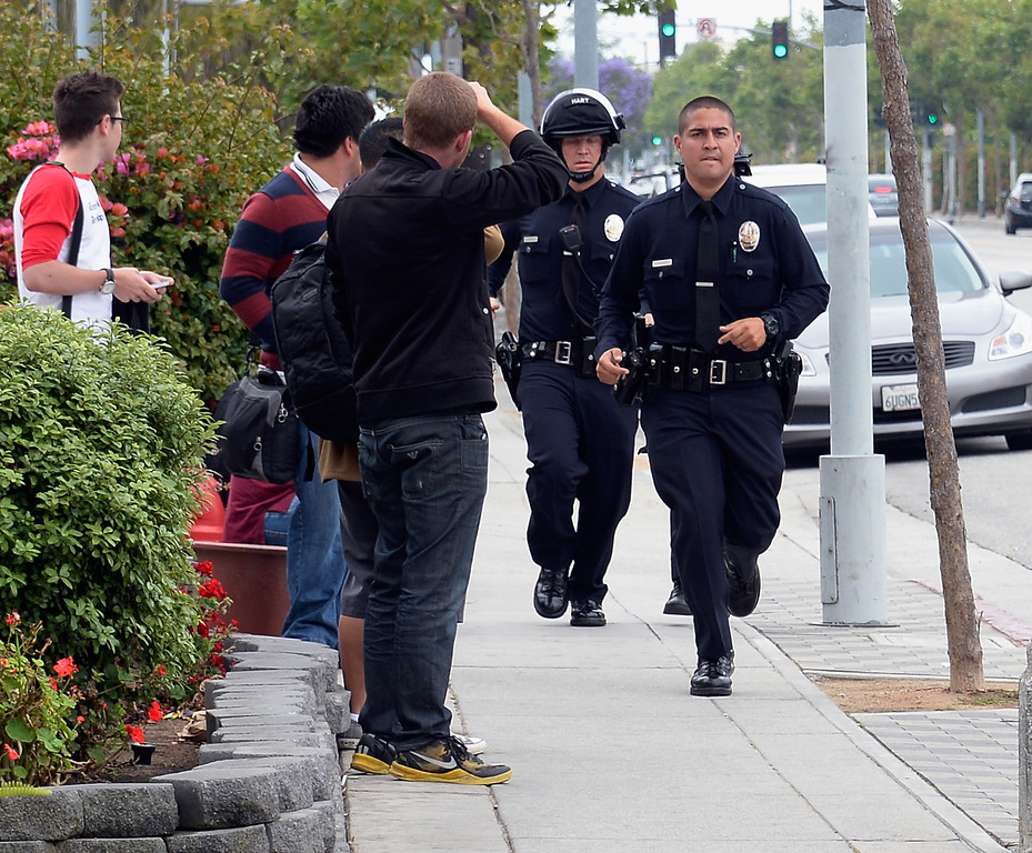 . SANTA MONICA, CA - JUNE 07: Students look on as Los Angeles Police Department officers deploy around the grounds of Santa Monica College near the library after multiple shootings  were reported on the campus June 7, 2013 in Santa Monica, California.  According to reports, at least three people have been injured, and a suspect was taken into custody. (Photo by Kevork Djansezian/Getty Images)