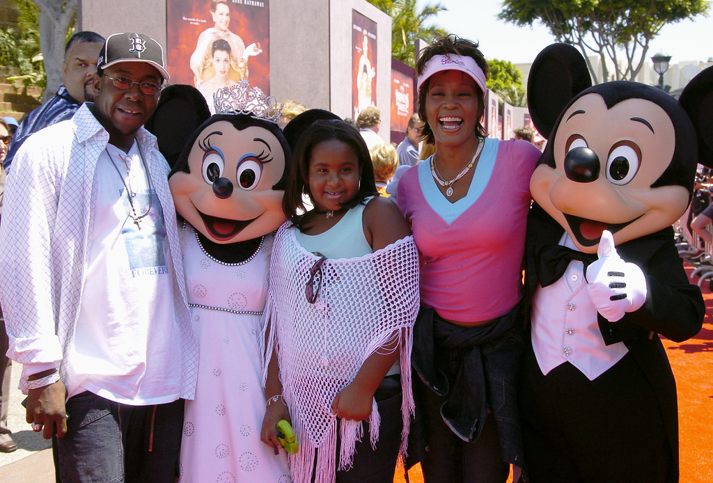""". In this handout image provided by Disney Parks, Whitney Houston, Bobby Brown and their daughter Bobbi Kristina are greeted by Mickey Mouse and Minnie Mouse for the premiere of \""""The Princess Diaries 2\"""" at the Disneyland Resort August 7, 2004 in Anaheim, California.  (Photo by Lisa Rose/Disney Parks via Getty Images)"""
