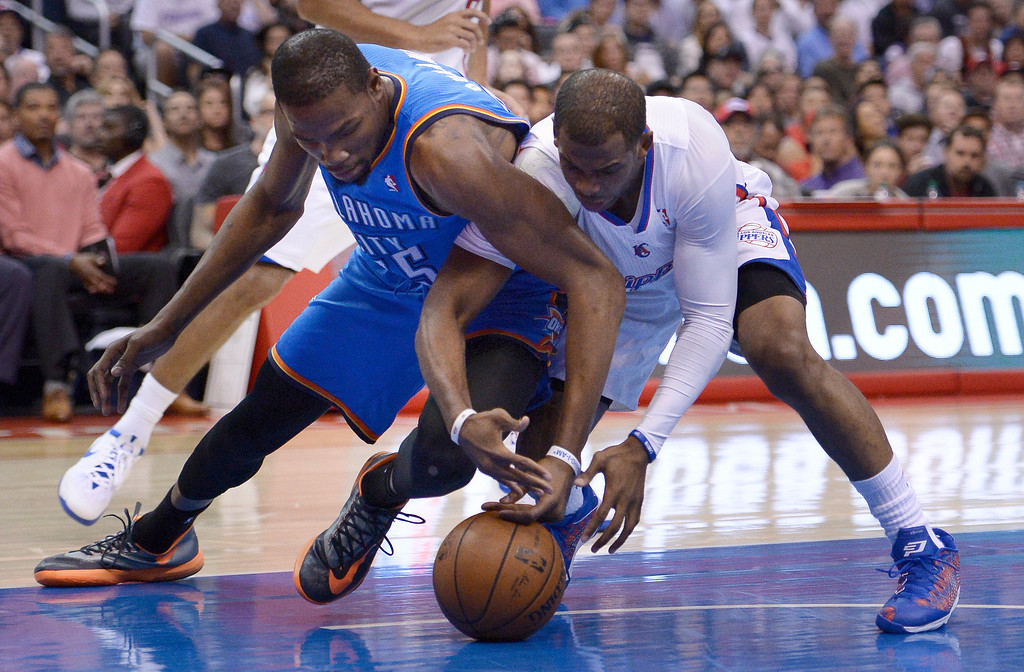 . Thunder#25 Thabo Sefolosha and Clippers#3 Chris Paul battle for a loose ball in the first half. The Los Angeles Clippers played the Oklahoma City Thunder in a regular season game at Staples Center in Los Angeles, CA. 4/9/2014(Photo by John McCoy / Los Angeles Daily News)