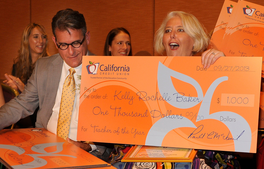 . Michael Hayden and Kelly Baker look surprised to receive $1500 checks from the California Credit Union. Sixteen teachers from throughout the Los Angeles County were named as Teachers of the Year during a ceremony at the Universal Hilton. Teachers received a cash award from the California Credit Union as well as software and hardware to use in their classrooms from eInstruction. Universal City, CA. 9/27/2013. photo by (John McCoy/Los Angeles Daily News)