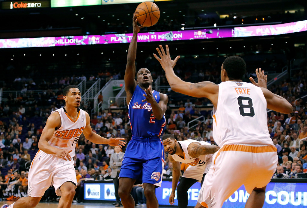 . Los Angeles Clippers guard Darren Collison (2) passes over Phoenix Suns forward Channing Frye (8) as Suns guard Gerald Green (14) defends during the first half of an NBA basketball game, Wednesday, April 2, 2014,in Phoenix. (AP Photo/Matt York)