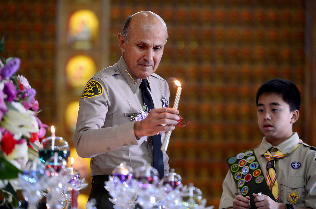 . Los Angeles County Sheriff Lee Baca lights a candle for peace with the help of Jeffrey Ho, 13, of Boy Scout Troop 8888, during the 2014 World Peace Ceremony at the Hsi Lai Temple in Hacienda Heights Saturday, January 4, 2014. (Photo by Sarah Reingewirtz/Pasadena Star-News)