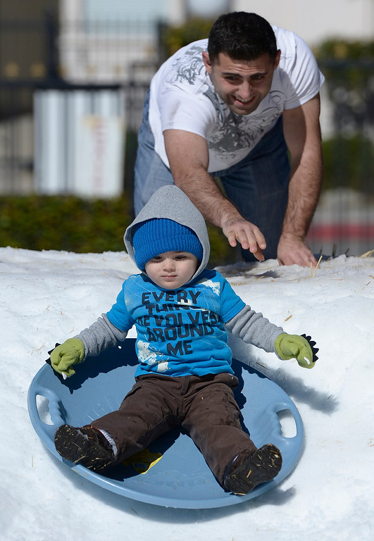 . John Melikyan pushes his son Aram,2, down the slope. The Armenian Relief Society is hosting a two-day Winter Wonderland event this weekend, with snow, entertainment, games and amusement rides. Held at the Armenian Apostolic Church in Glendale.  Glendale, CA. February 1, 2014 (Photo by John McCoy / Los Angeles Daily News)