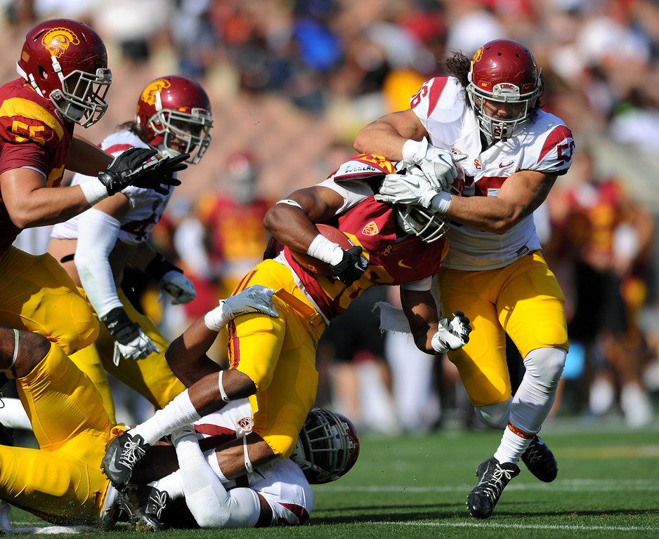 . USC RB James Toland is stopped by LBs Jabari Ruffin, bottom, and Anthony Sarao during their spring game, Saturday, April 19, 2014, at the Coliseum. (Photo by Michael Owen Baker/L.A. Daily News)