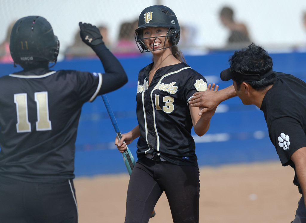 . Peninsula\'s Savanna Norcio (11), Alejandra Magana (13) and assistant coach Roman Hernandez celebrate as they start the scoring against North in a first round CIF SS Division III softball game Thursday in Torrance. Peninsula won 4-1. 20130516 Photo by Steve McCrank / Staff Photographer