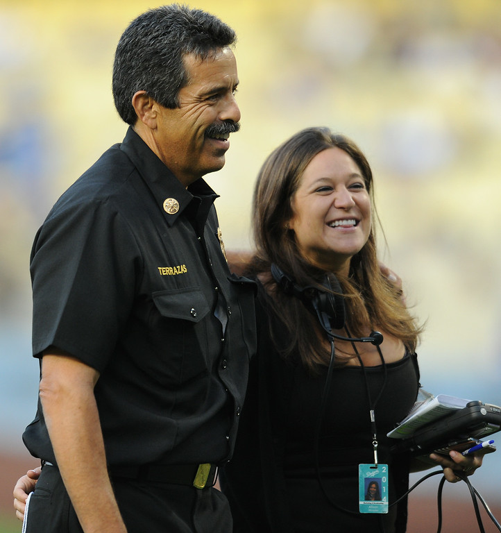 . Newly installed LAFD Chief Ralph Terrazas is escorted by Dodgers Allison Mossler after he threw out the first pitch at Dodger Stadium, as the team hosts the San Diego Padres at the inaugural Firefighter Appreciation Night. Los Angeles, CA. 8/19/2014(Photo by John McCoy Daily News)