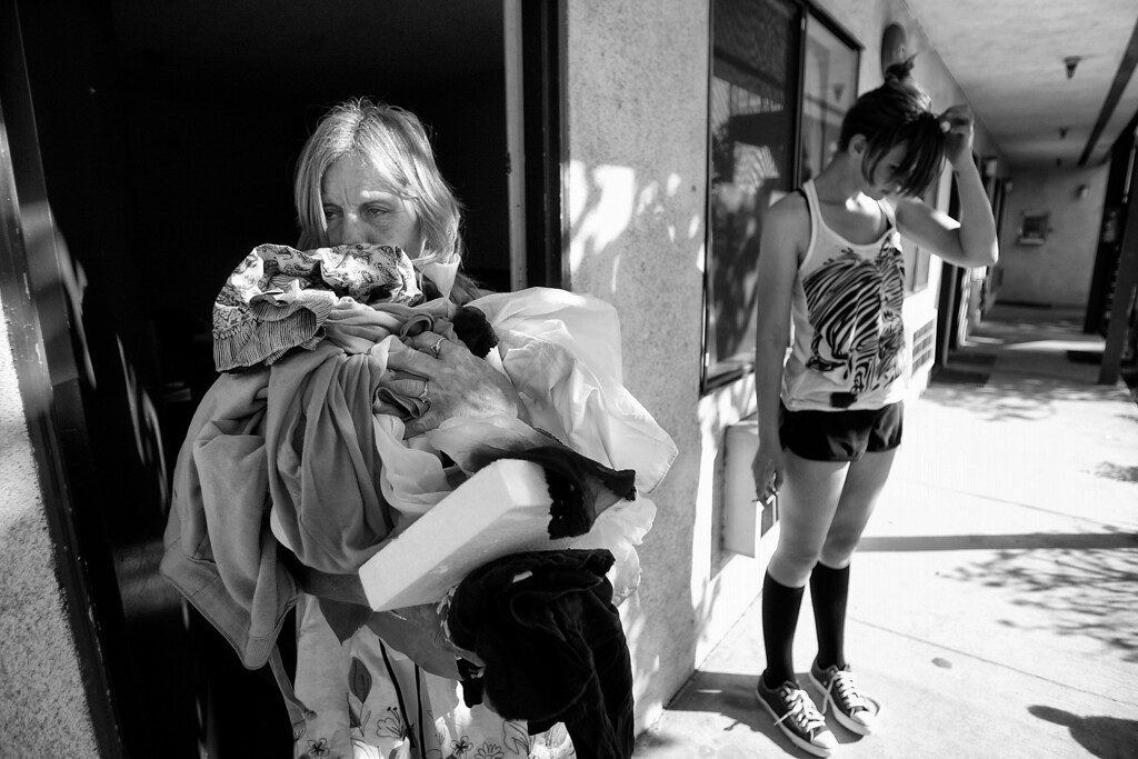 . Dorothy sorts and organizes her clothes at an east Pasadena motel while Candice, who is homeless, stops by for a visit.  (Photos by Sarah Reingewirtz / Pasadena Star-News)