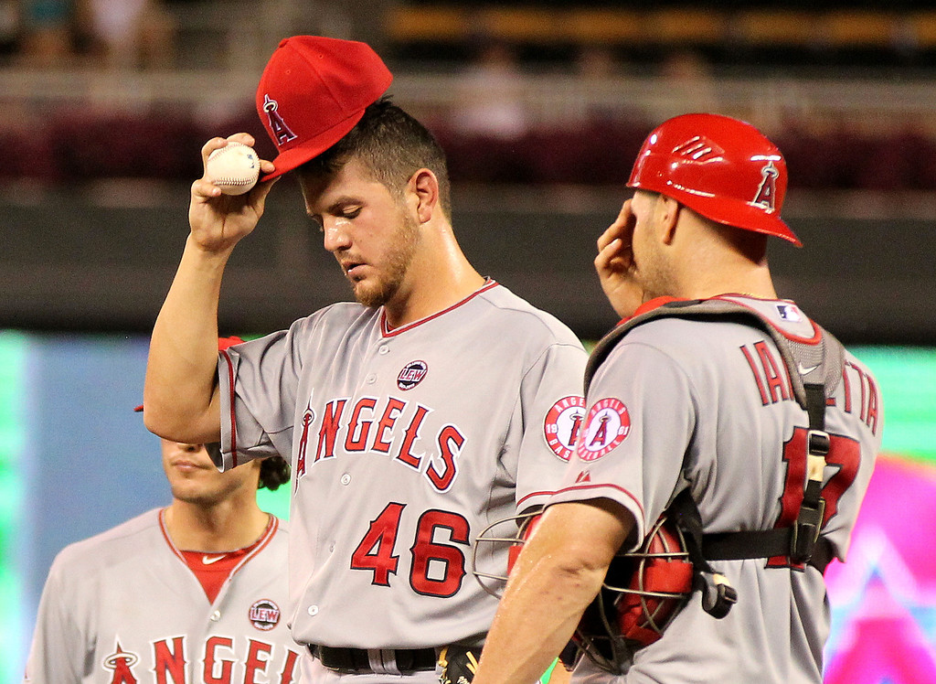 . Los Angeles Angels pitcher Cory Rasmus (46) is dejected after giving up a sacrifice fly with catcher Chris Iannetta, right, against the Minnesota Twins in the seventh inning of their baseball game won by the Twins 6-3 in Minneapolis Monday, Sept. 9, 2013.(AP Photo/Andy Clayton-King)