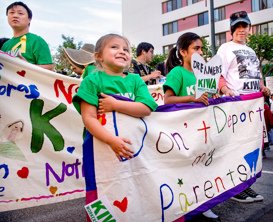 . Sasha Carmen, 4, from left, Sarai Sanchez, 7, and Tais Morales carry a sign opposing deportation of undocumented immigrants.  The Coalition for Humane Immigrant Rights of Los Angeles (CHIRLA) joined area organizations and coalitions to march in honor of worker contributions and denounce deportations of undocumented immigrants living in the United States May 1, 2014.   (Staff photo by Leo Jarzomb/San Gabriel Valley Tribune)