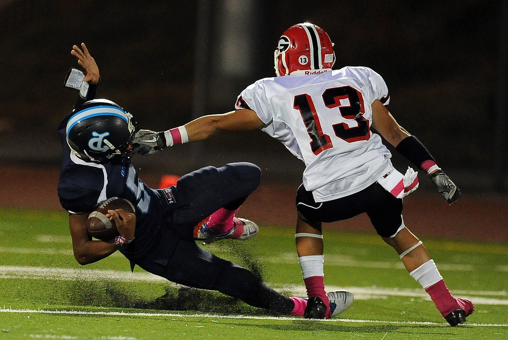 . Duarte\'s Darryl Robinson (5) catches a pass over Gladstone\'s Steven Gutierrez (13) in the first half of a prep football game at Duarte High School in Duarte, Calif., Thursday, Oct. 10, 2013.    (Keith Birmingham Pasadena Star-News)