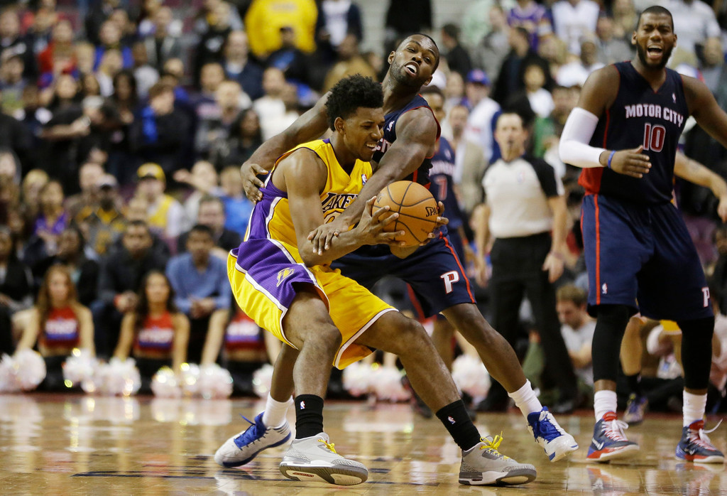 . Detroit Pistons guard Rodney Stuckey reaches in and fouls Los Angeles Lakers  forward Nick Young (0) in the closing seconds of their NBA basketball game at the Palace in Auburn Hills, Mich., Friday, Nov. 29, 2013. (AP Photo/Carlos Osorio)