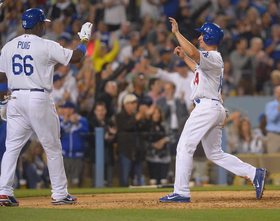 . Dodgers second baseman Mark Ellis is congratulated by Yasiel Puig after crossing the plate to tie the game in the 6th inning against the Mets August 12, 2013.  The Dodgers are hosting the Mets for a three game series.(Andy Holzman/Los Angeles Daily News)