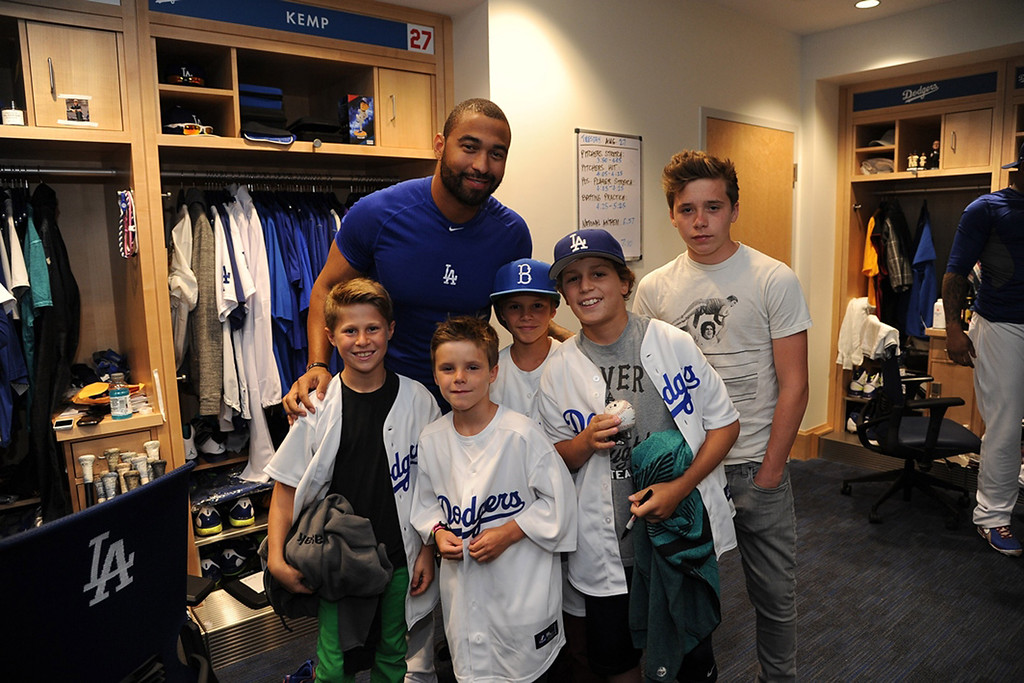 . In this handout photo provided by the Los Angeles Dodgers, Los Angeles Dodger player Matt Kemp poses with Cruz Beckham (2nd Left), Romeo Beckham (C), Brooklyn Beckham (R) and other young fans in the clubhouse at Dodger Stadium on August 27, 2013 in Los Angeles, California. (Photo by Jon Soohoo/LA Dodgers via Getty Images)