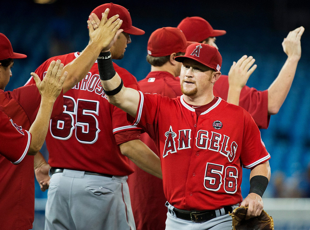 . Los Angeles Angels right fielder Kole Calhoun, right, celebrates with teammates after they defeated the Toronto Blue Jays in ninth-inning AL baseball game action in Toronto, Wednesday, Sept. 11, 2013. (AP Photo/The Canadian Press, Nathan Denette)