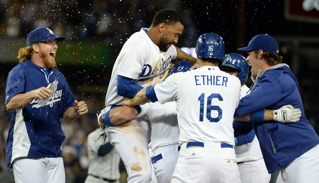 . Los Angeles Dodgers\' A.J. Ellis is mobbed by teammates after a game winning sac fly ball as Adrian Gonzalez (not pictured) scores the winning run in the ninth inning as the Los Angeles Dodgers defeat the San Diego Padres 1-0 during a Major league baseball game on Saturday, July 12, 2014 in Los Angeles.   (Keith Birmingham/Pasadena Star-News)