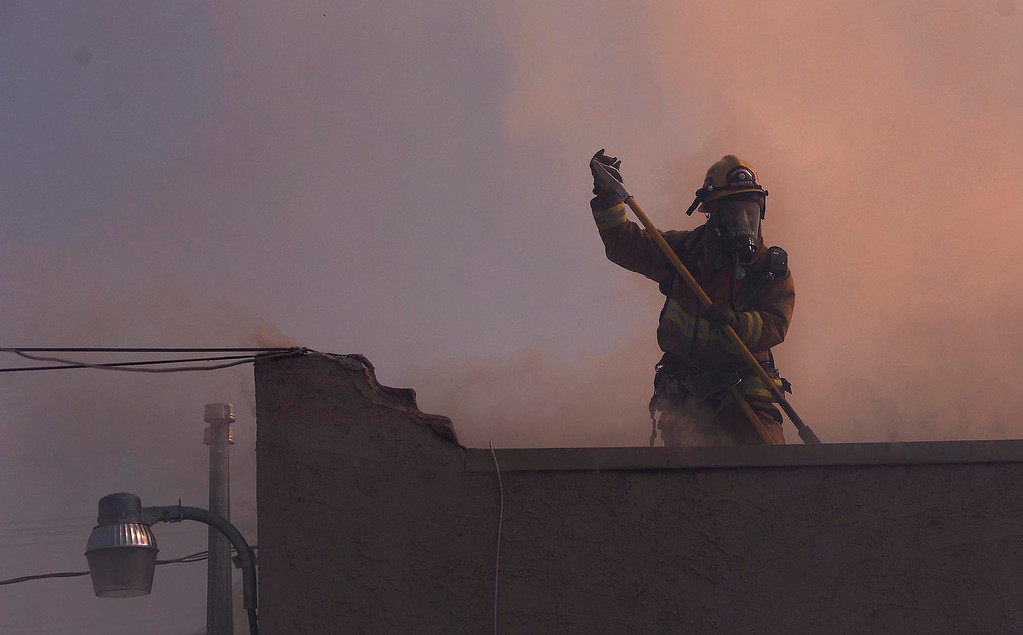 . A firefighter works atop a roof of a residence involved in a four-alarm fire along the 700 block of Seventh Street in San Bernardino August 18, 2013.  The fire displaced dozens of people from an apartment complex.  GABRIEL LUIS ACOSTA/STAFF PHOTOGRAPHER.