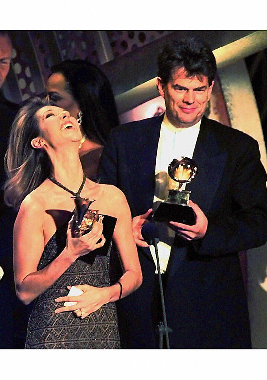 """. NEW YORK, UNITED STATES:  Celine Dion (L) smiles as David Foster looks on 26 February at the Grammy Awards in New York. Dion won for best Pop Album and Album of the Year for \""""Falling Into You.\""""  (TIMOTHY CLARY/AFP/Getty Images)"""