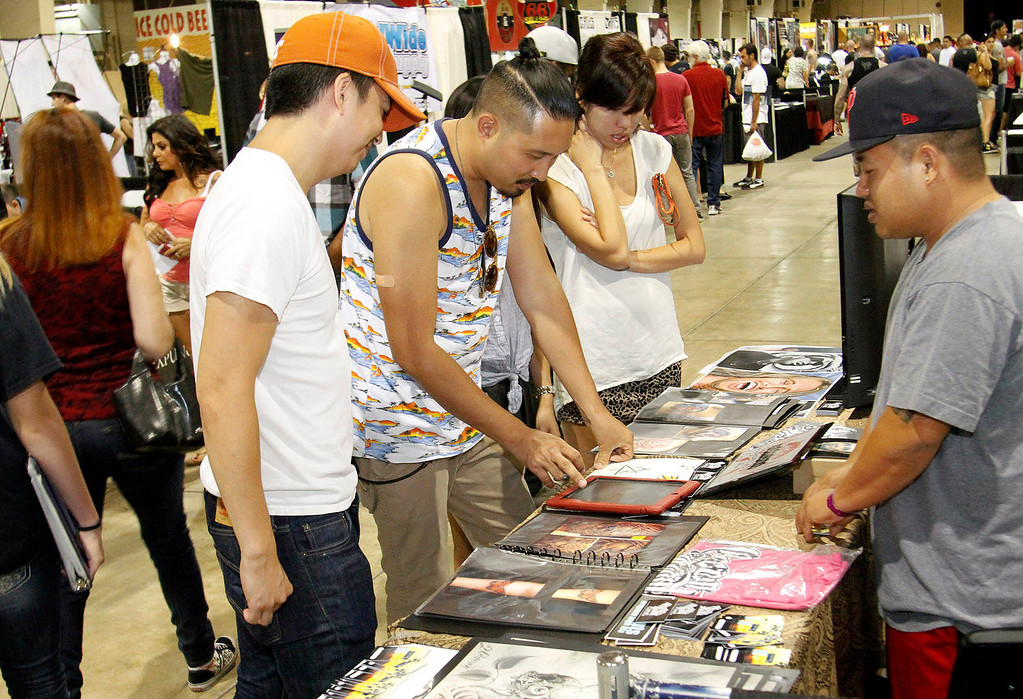 . (Correspondent Photo by James Carbone) People look over different drawings for a tattoo, during the Tattoo and Body Art Expo, the world\'s largest tattoo expo, comprised of more than 300 tattoo artists and piercers, at the Pomona Fairplex, in Pomona, Saturday, July 11, 2013.