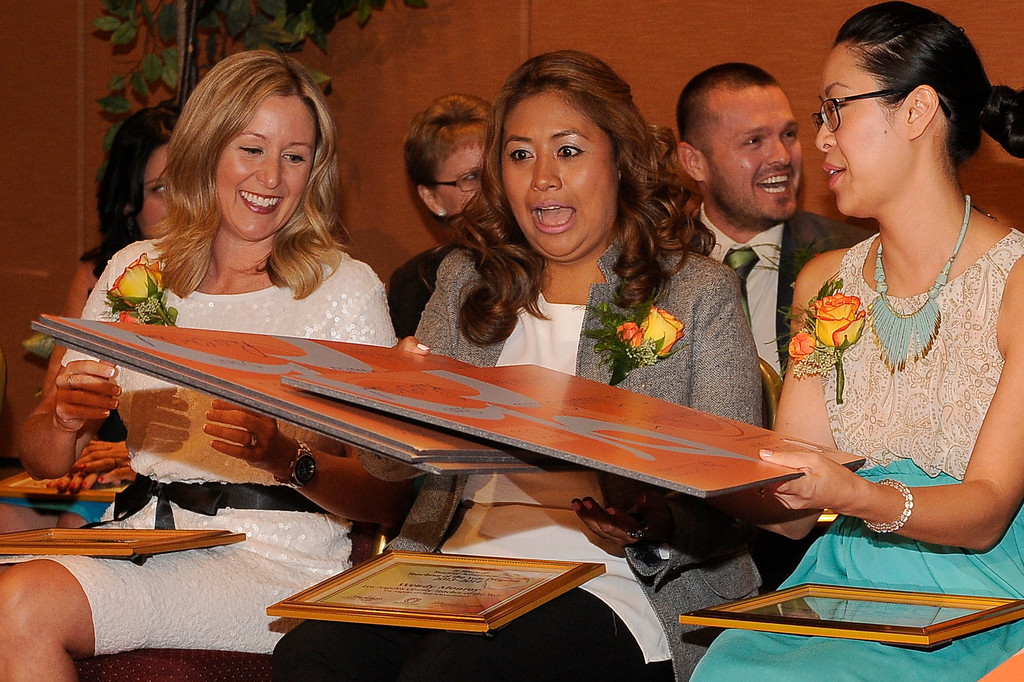 . (l-r) Kimberly Dueñas Wendy Monroy and Beth Katz wrestle with $1500 checks awarded to them by the California Credit Union. Sixteen teachers from throughout the Los Angeles County were named as Teachers of the Year during a ceremony at the Universal Hilton. Teachers received a cash award from the California Credit Union as well as software and hardware to use in their classrooms from eInstruction. Universal City, CA. 9/27/2013. photo by (John McCoy/Los Angeles Daily News)