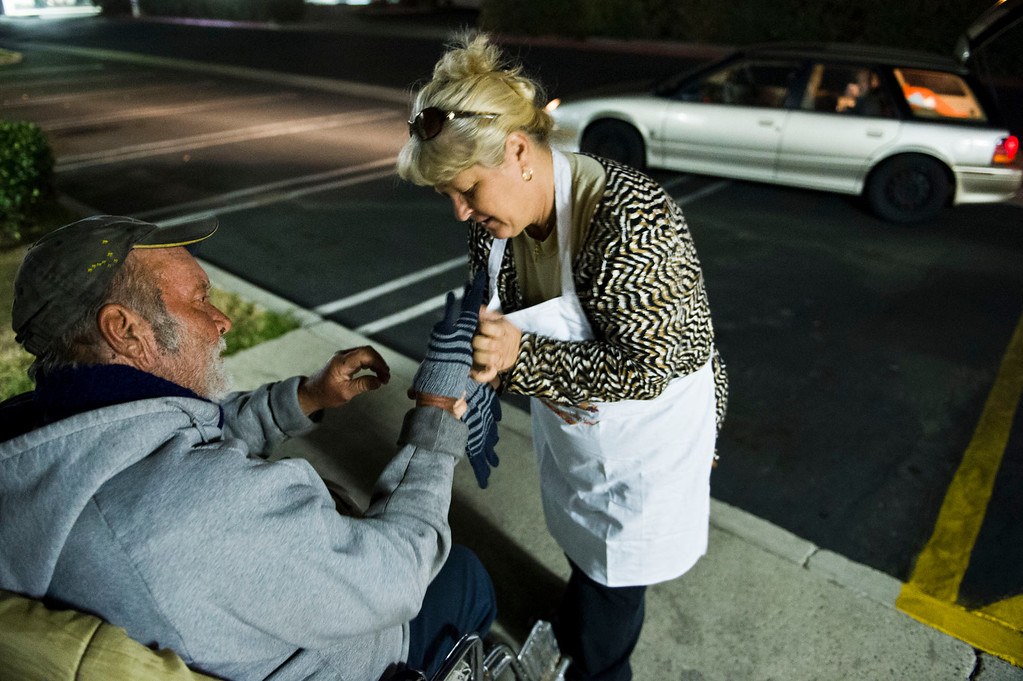 . Nicolette Wingert, right, puts new gloves on to a homeless man who is handicap in Covina on Wednesday night, Nov. 27, 2013. Nicolette Wingert has been feeding the homeless six days a week for the past seven years with Nurses4Christ, a nonprofit organization she founded in 2006. She and Phillip Stern of Glendora have been going every day since 2008, feeding homeless people sandwiches and hot food; giving them bottles of water, clothes and blankets. (Photo by Watchara Phomicinda/San Gabriel Valley Tribune)