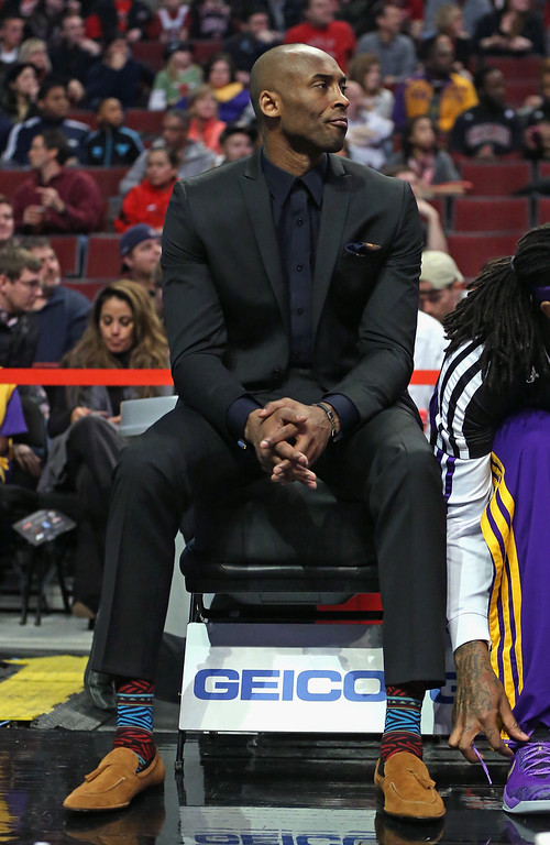 . Kobe Bryant #24 of the Los Angeles Lakers watches from the bench as his teammates take on the Chicago Bulls at the United Center on January 20, 2014 in Chicago, Illinois.   (Photo by Jonathan Daniel/Getty Images)