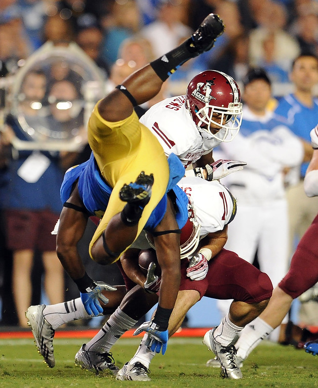 . UCLA linebacker Jayon Brown (19) hits New Mexico State wide receiver Adam Shapiro (7) on a kick-off return during the first half of their college football game in the Rose Bowl in Pasadena, Calif., on Saturday, Sept. 21, 2013.   (Keith Birmingham Pasadena Star-News)