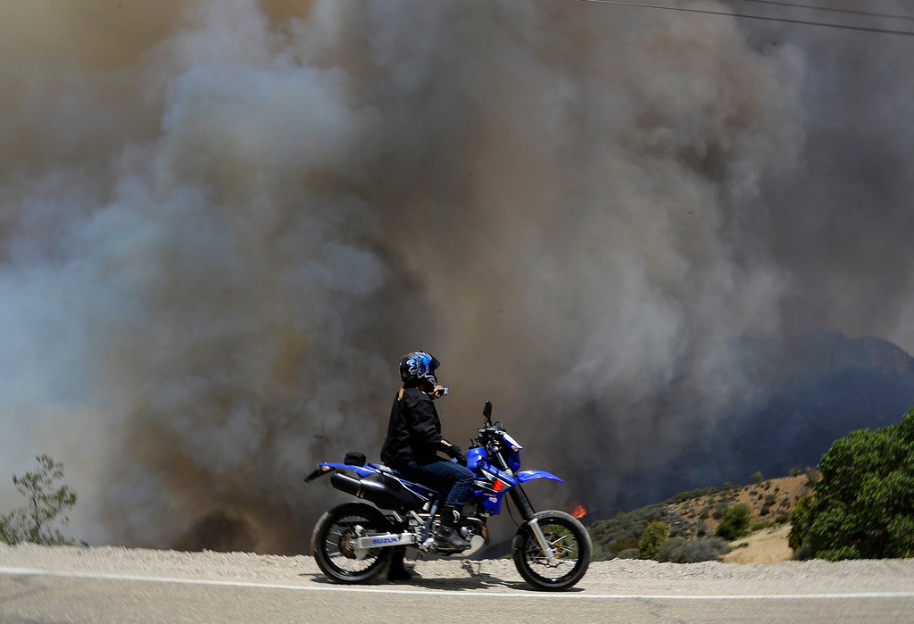 . A local resident on a motorcycle takes photos as smoke goes up like a volcano in the canyon areas during the second day of the Springs Fire in the mountain areas of Ventura County CA.  May 3, 2013. A fierce, wind-whipped brush fire spread on Friday along the California coast northwest of Los Angeles, threatening several thousand homes and a military base as more than 1,100 dwellings were ordered evacuated and a university campus was closed. May 2,2013. Ventura County California.  Photo by Gene Blevins/LA Daily News