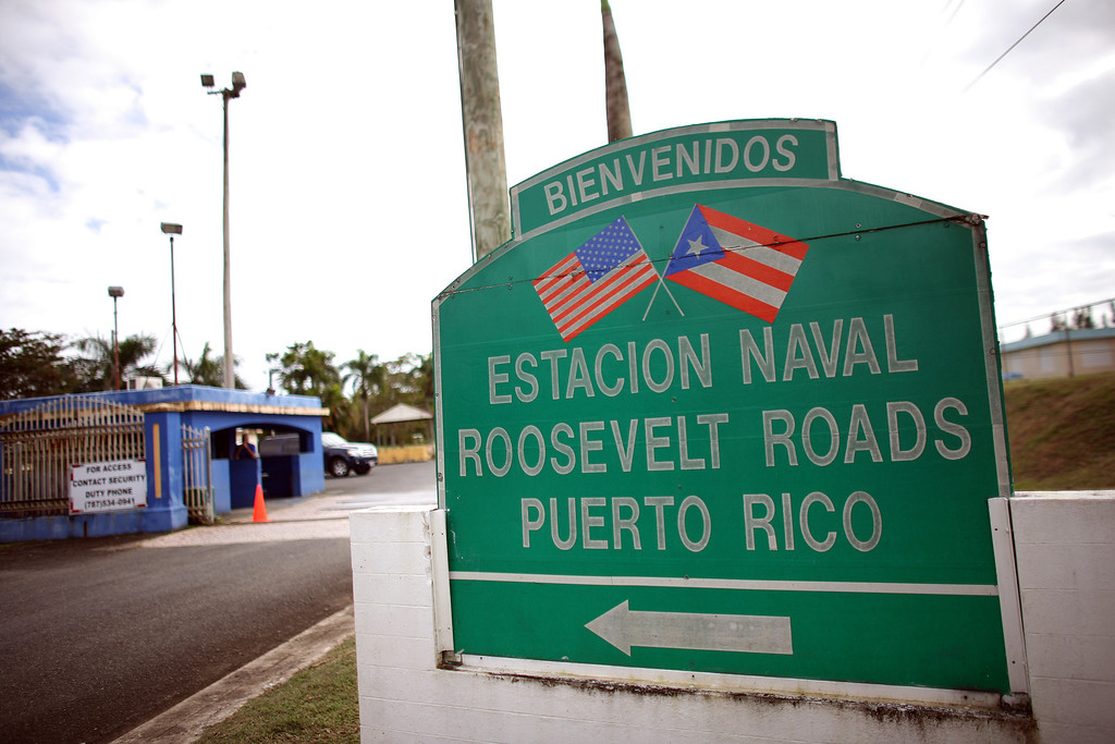 . In this photo taken on Jan. 25, 2012, a welcome sign stands at the entrance of the former Naval Station Roosevelt Roads in Ceiba, Puerto Rico.  The U.S. Navy is looking for a buyer for the former naval station, once the hub of U.S. military operations in the Caribbean that closed in 2004 after the Navy stopped using nearby Vieques as a bombing range.  (AP Photo/Ricardo Arduengo)