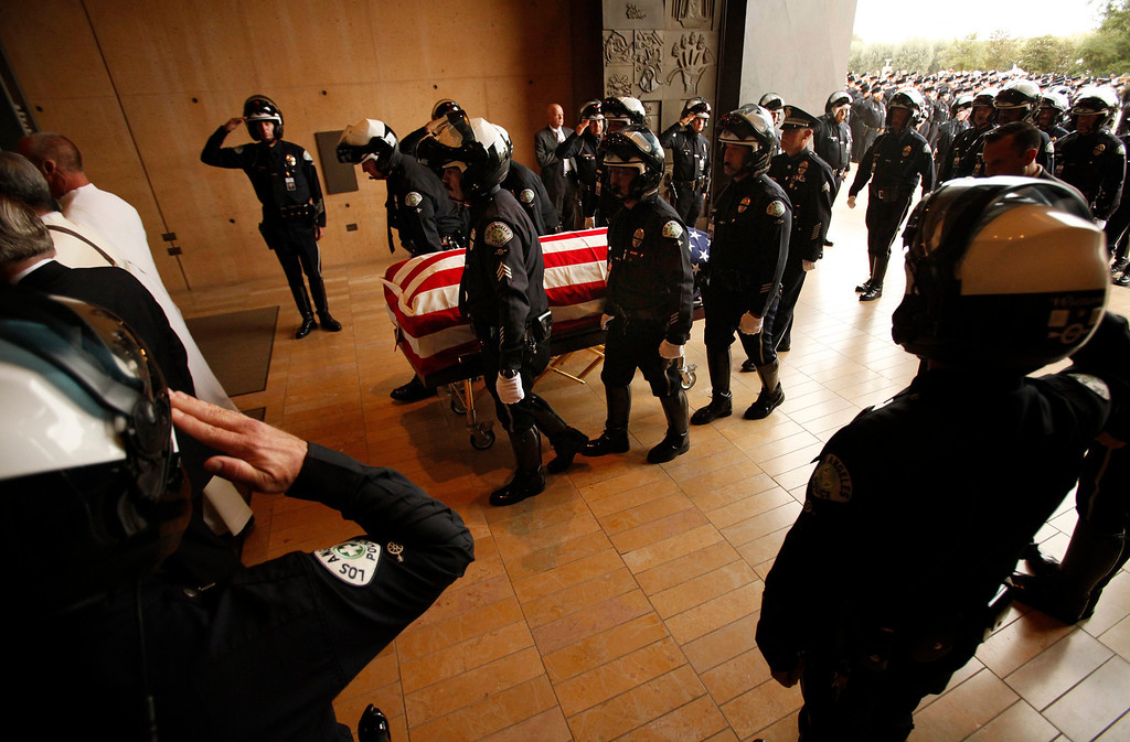 . Pallbearers escort the the coffin of Los Angeles Police Dept. motorcycle officer Chris Cortijo during a funeral service at the Cathedral of Our Lady of the Angels Tuesday morning, April 22, 2014, in Los Angeles. Hundreds of fellow law enforcement officers turned out to mourn 51-year-old officer, who died after he was struck by a motorist allegedly under the influence of cocaine on April 5. (AP Photo/Los Angeles Times, Al Seib, Pool)
