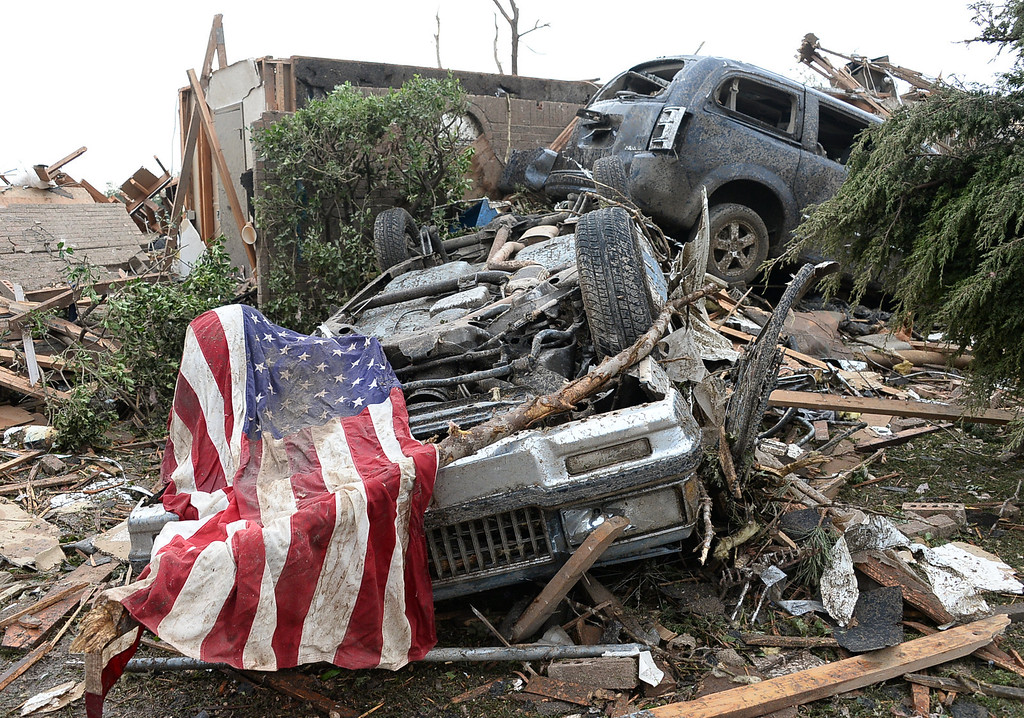 . An American flag lays on one of many destroyed cars. 
