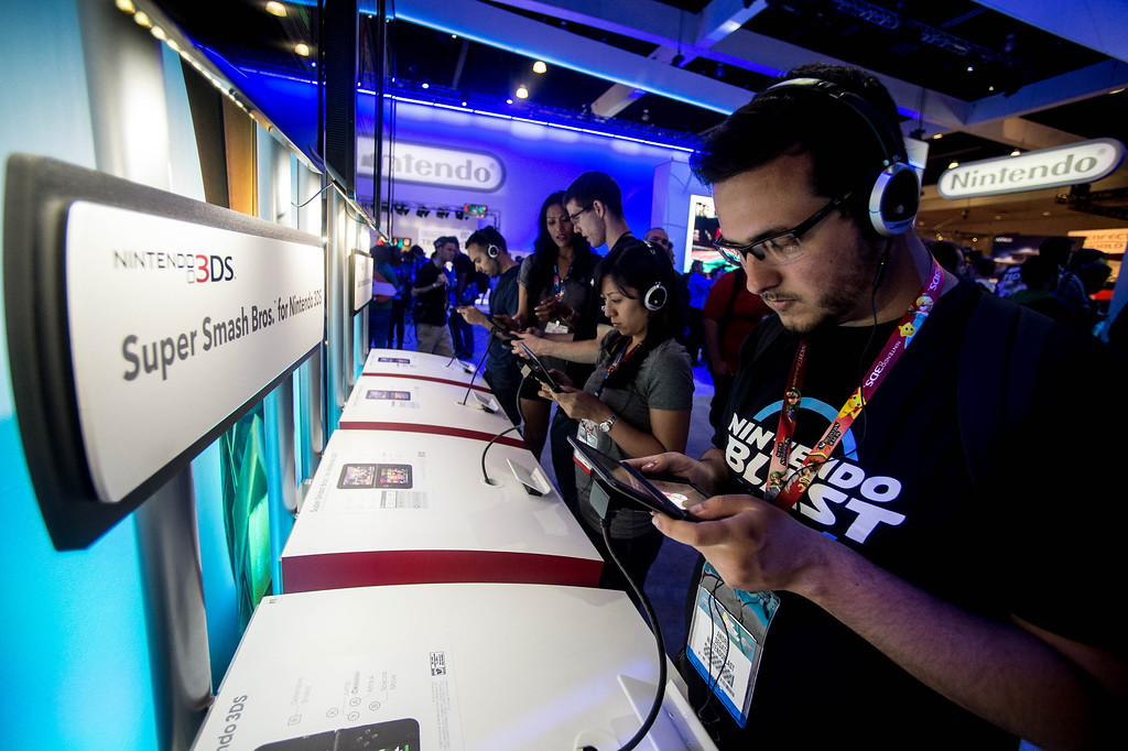 """. Attendees play the \""""Super Smash Bros\"""" video game on the Nintendo 3DS at at the Electronic Entertainment Expo in Los Angeles on Tuesday, June 10, 2014. (Photo by Watchara Phomicinda)"""