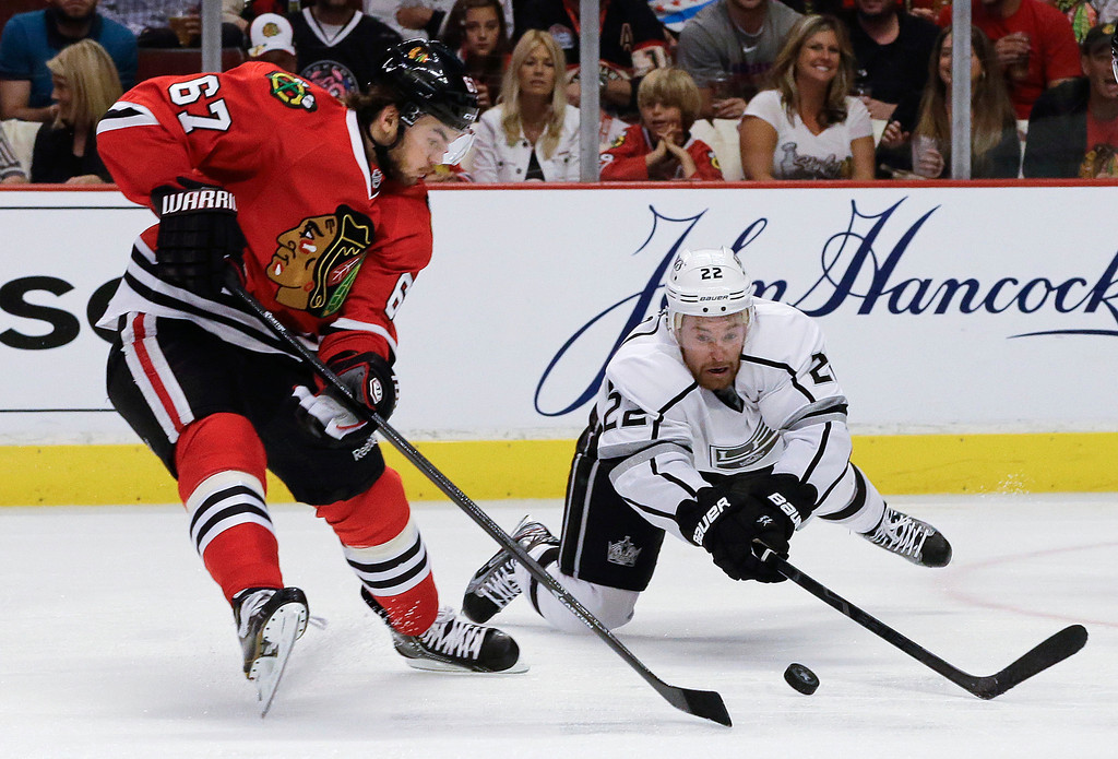 . Los Angeles Kings center Trevor Lewis (22) dives for the puck against Chicago Blackhawks center Michael Frolik (67) during the second period of Game 1 of the NHL hockey Stanley Cup Western Conference finals, Saturday, June 1, in Chicago. (AP Photo/Nam Y. Huh)