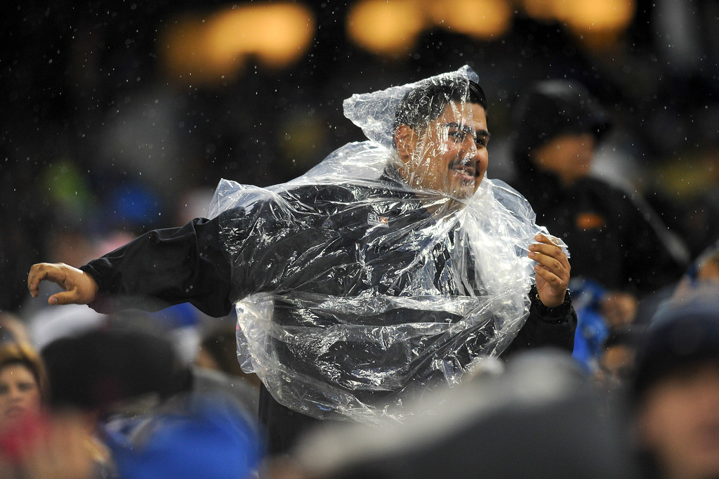 . Dodgers security personnel cover up against the rain, Friday, April 25, 2014, at Dodger Stadium. (Photo by Michael Owen Baker/L.A. Daily News)