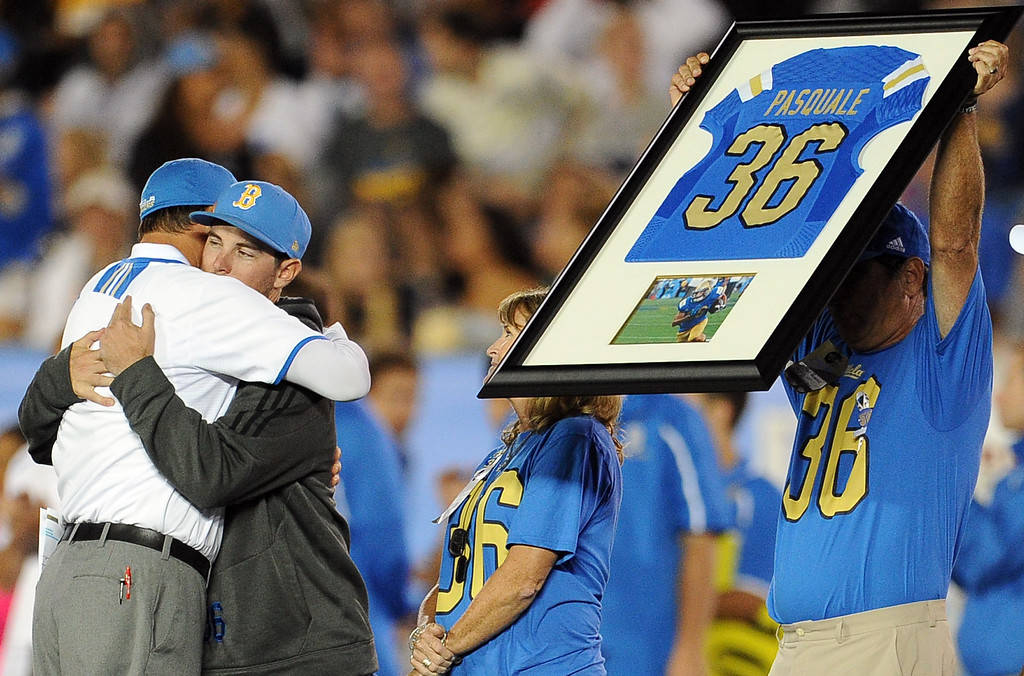. UCLA head football coach Jim Mora, left, hugs AJ, the brother of Nick as his parents Mel (holding jersey) and Laurie Pasquale look on during a ceremony between the 1st and 2nd quarter their college football game against New Mexico State in the Rose Bowl in Pasadena, Calif., on Saturday, Sept. 21, 2013. Nick Pasquale, the UCLA receiver was struck and killed by a car on Sept. 8th.   (Keith Birmingham Pasadena Star-News)