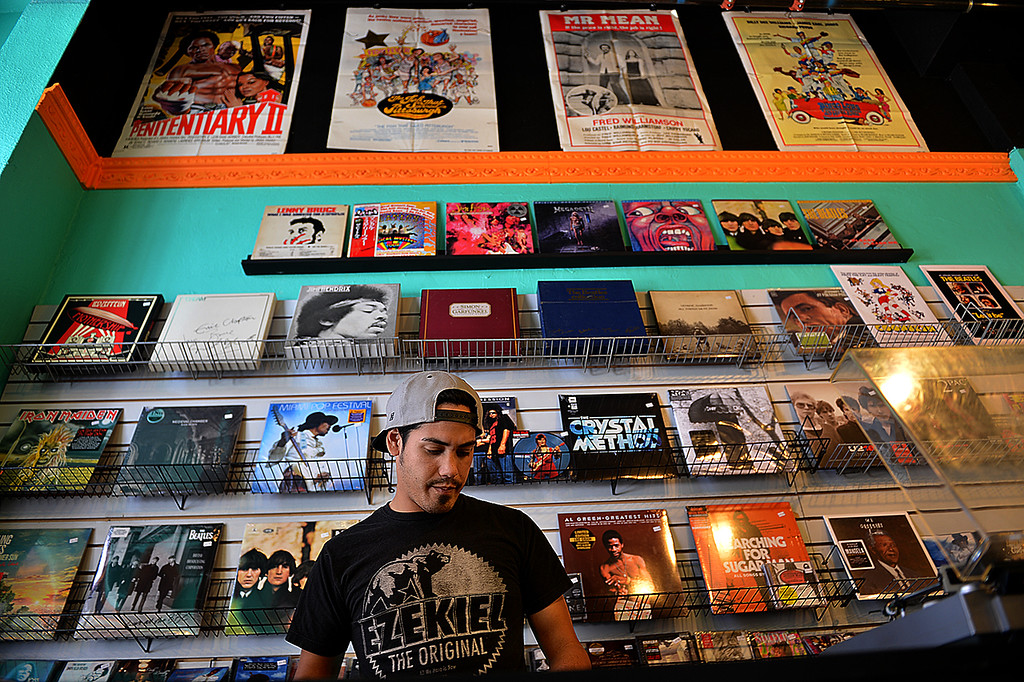. Mauricio Morgan, 26, says, listening to music all day, is just one of the benefits working the counter at Redlands second store offering vinyl records. Redlands Vinyl Records and Collectibles recently opened its doors in Redlands to offer a second place in town to collect records and other collectibles.  (Photo by Rick Sforza/Redlands Daily Facts)