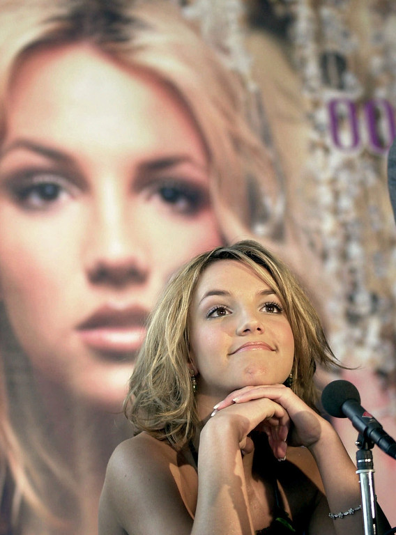 ". The 18-year-old U.S. pop star Britney Spears sits in front of her poster during a news conference in Cologne, Germany, Monday, April 17, 2000, where she presented her new album ""oops!... I did it again.\"" (AP Photo/Hermann J. Knippertz)"