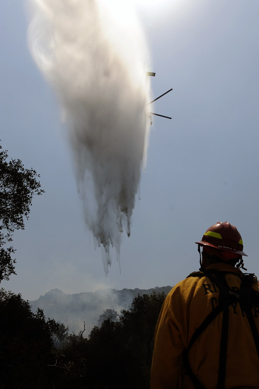 . A sky crane drops water on a hotspot as Riverside City Fire Captain Sean Smith watches along Potrero Road in Newbury Park, Saturday, May 4, 2013. (Michael Owen Baker/Staff Photographer)
