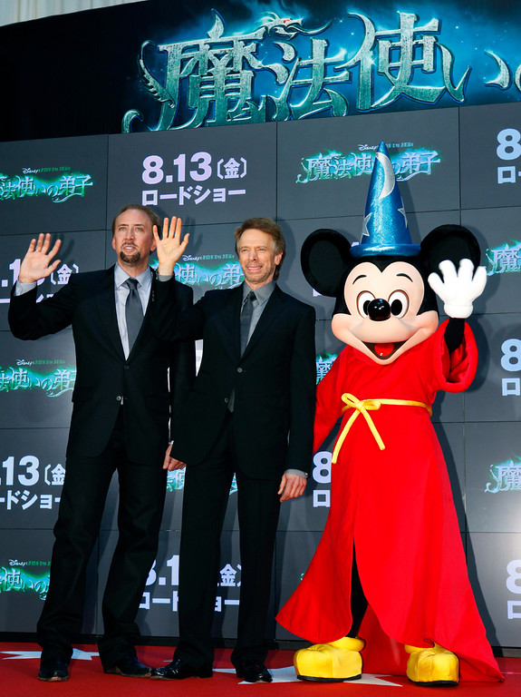 """. Actor Nicolas Cage, left, and producer Jerry Bruckheimer, center, pose for photographers along side Mickey Mouse during the Japan premiere of their latest movie \""""The Sorcerer\'s Apprentice\"""" in Tokyo, Wednesday, July 21, 2010. (AP Photo/Shizuo Kambayashi)"""