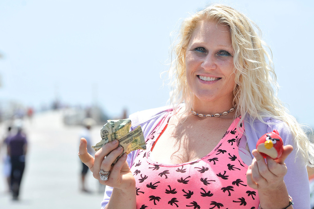 . HERMOSA BEACH PIER - 05/31/2014 - (Mark Savage) Jackie Hatten, one of the owners of Tiki Mon, found an Angry Bird with $80 near the volleyball court on the beach.  The �hidden cash� craze moved to the beach on Saturday, with a clue first seemingly pointing to Mother�s Beach. So early morning diggers showed up in Marina del Rey and Long Beach. But then the anonymous cash stasher revealed the spot to be Hermosa Beach, where traffic backed up for miles as hunters found plastic red birds filled with bills.