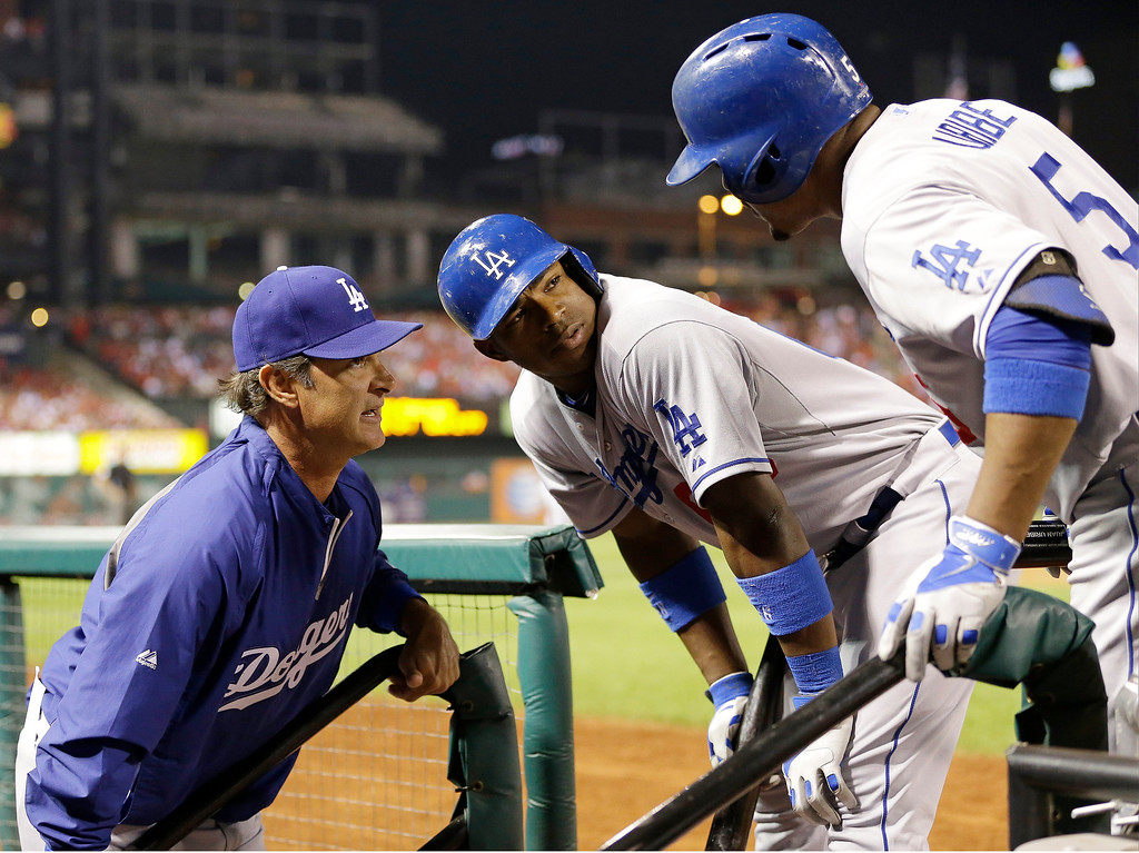 . Los Angeles Dodgers manager Don Mattingly talks to Juan Uribe (5) and Yasiel Puig during the eighth inning of Game 1 of the National League baseball championship series against the St. Louis Cardinals, Friday, Oct. 11, 2013, in St. Louis. (AP Photo/David J. Phillip)