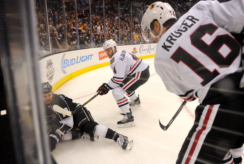 . The Kings\' Kyle Clifford is knocked down by the Blackhawks\' Niklas Hjalmarsson (#4) as Marcus Kruger secures the puck during game six of the Western Conference Finals, Friday, May 30, 2014, at Staples Center. (Photo by Michael Owen Baker/Los Angeles Daily News)