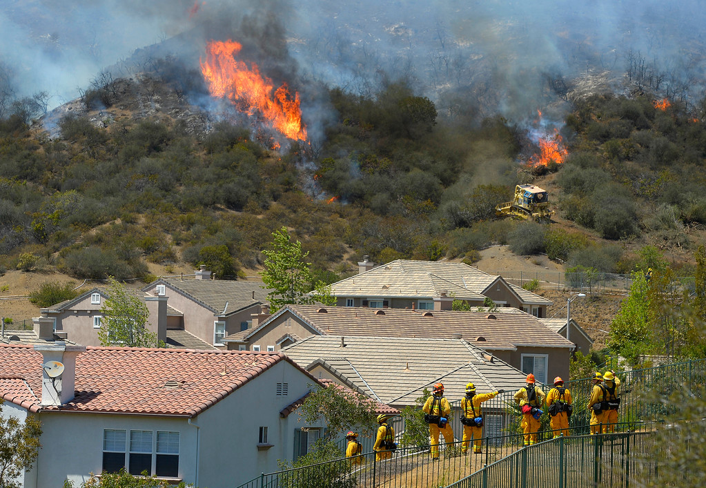 . Firefighters stand watch as bulldozers clear a firebreak near a wildfire burning along a hillside near homes in Thousand Oaks, Calif., Thursday, May 2, 2013. A Ventura County Fire Department spokeswoman said the blaze that broke out Thursday morning near Camarillo and Thousand Oaks, 50 miles west of Los Angeles, had spread to over 6,500 acres, forcing evacuations of nearby neighborhoods. (AP Photo/Mark J. Terrill)