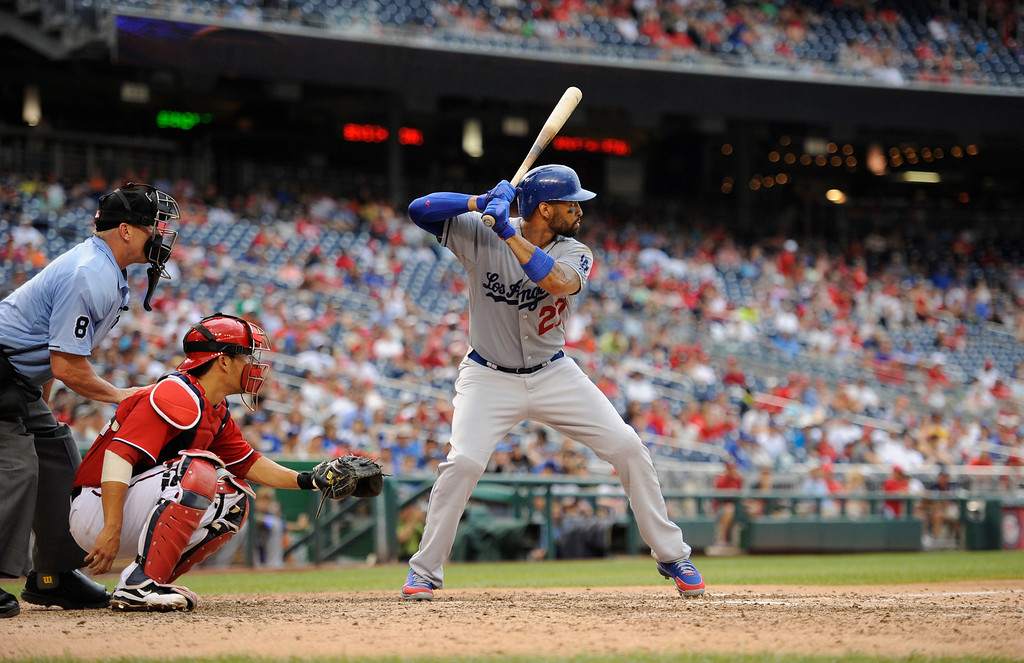 . Los Angeles Dodgers\' Matt Kemp (27) bats during the ninth inning of a baseball game, Sunday, July 21, 2013, in Washington. Also seen are Washington Nationals catcher Kurt Suzuki, center, and home plate umpire Jeff Kellogg (8). The Dodgers won 9-2. (AP Photo/Nick Wass)