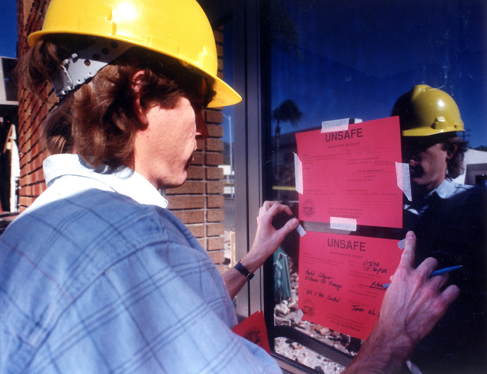 . Structural engineer Tom Henson puts red tags on a building on Central Avenue in Fillmore.  The tags declare that the building is unsafe.   Los Angeles Daily News file photo