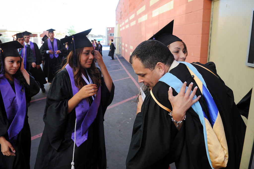 . Jose Navarro, principal of Social Justice Humanitas Academy, right, hugs students before their graduation at the Cesar Chavez Learning Academies in San Fernando, Wednesday, June 5, 2013. (Michael Owen Baker/Staff Photographer)