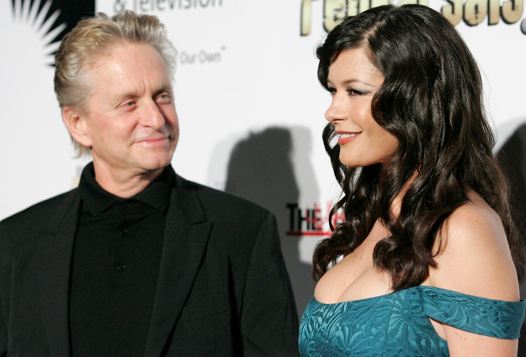 ". Actor Michael Douglas, left and wife actress Catherine Zeta-Jones, right, pose on the press line at ""A Fine Romance\"" Benefit in Los Angeles on Saturday, Nov. 18, 2006. (AP Photo/Dan Steinberg)"