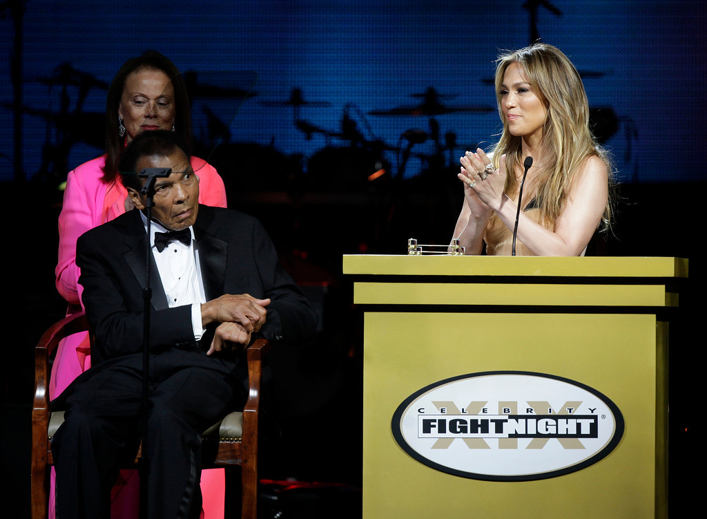 . Actress and entertainer Jennifer Lopez, right, applauds at Muhammad Ali\'s Celebrity Fight Night XIX at the JW Marriott Desert Ridge Resort and Spa, as Ali and his wife, Lonnie, look on, Saturday, March 23, 2013, in Phoenix. (Photo by Rick Scuteri/Invision/AP)
