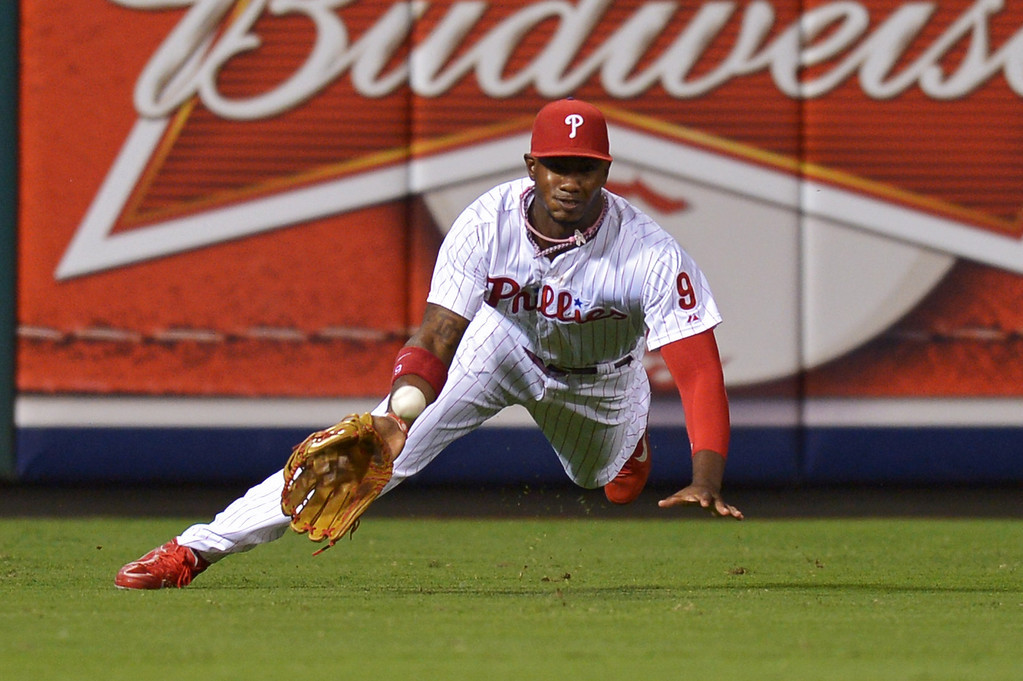 . PHILADELPHIA, PA - AUGUST 16: Domonic Brown #9 of the Philadelphia Phillies is unable to make the diving catch on a double hit by Mark Ellis #14 of the Los Angeles Dodgers in the seventh inning at Citizens Bank Park on August 16, 2013 in Philadelphia, Pennsylvania. The Dodgers won 4-0. (Photo by Drew Hallowell/Getty Images)